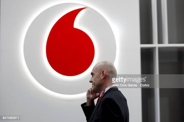 A congress attendant speaks on his smartphone in front of the Vodafone company logo on their stand during the Mobile World Congress on March 1 2017...