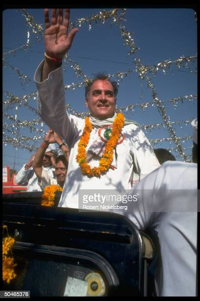 Congress ldr exPM Rajiv Gandhi waving to supporters riding in open vehicle campaigning for May parliamentary election in Uttar Pradesh state
