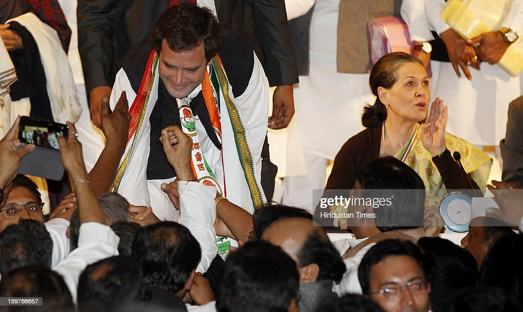 Congress leader Rahul Gandhi greets by the delegates while his mother and congress President Sonia Gandhi looks on during the AICC meeting after the two days 'Chintan Shivir' at Birla Auditorium, Jaipur on January 20, 2013 in Rajasthan, India.
