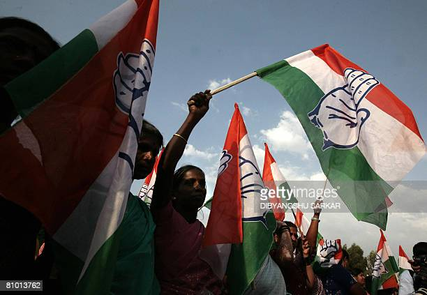 Congress Party activists wave party flags to welcome Congress Party President Sonia Gandhi during an election rally in Bangalore on May 7 2008 Gandhi...