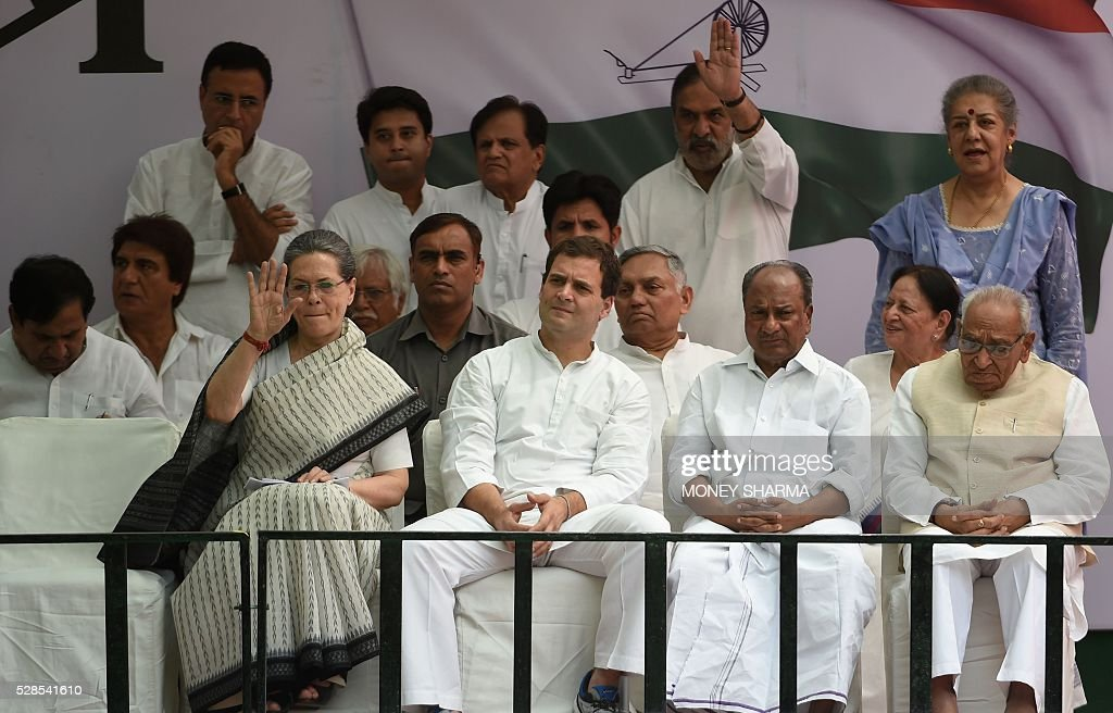 Congress Party president Sonia Gandhi (L) waves to supporters as party Vice-president Rahul Gandhi looks on during an anti-government protest in New Delhi on May 6, 2016. Former Indian prime minister Manmohan Singh, Congress Party President Sonia Gandhi and party Vice-president Rahul Gandhi were briefly arrested at a police station and later released during a 'Save Democracy' protest march against the ruling Bharatiya Janata Party (BJP). / AFP / MONEY
