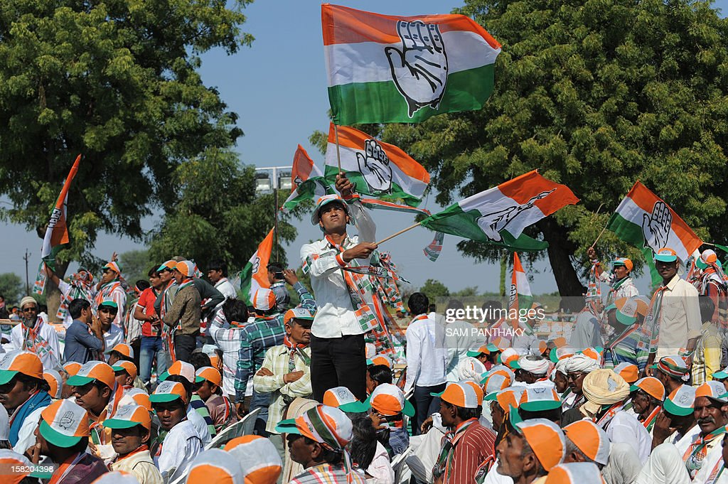 Congress Party supporters wave their party flags during a Congress rally addressed by general secretary, Rahul Gandhi ahead of the Gujarat Assembly polls at Sanand town, some 30 kms from Ahmedabad on December 11, 2012. Gujarat state of Western India goes to polls in two phases, December 13 and 17, 2012. AFP PHOTO / Sam PANTHAKY