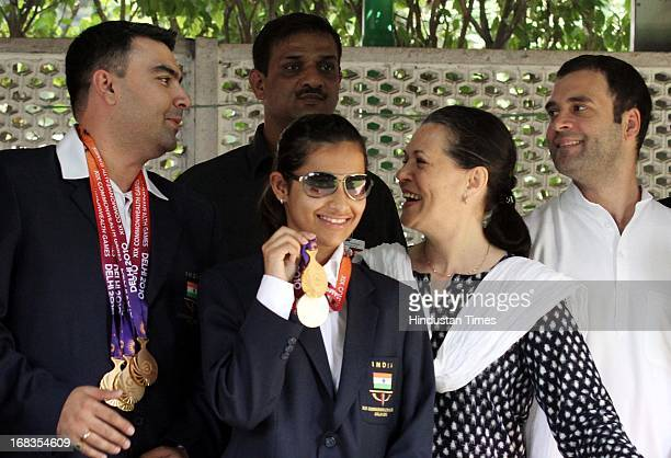 Congress President Sonia Gandhi and her son Rahul Gandhi pose for a photo with Indian shooters Gagan Narang Heena Sidhu others who won medals in the...