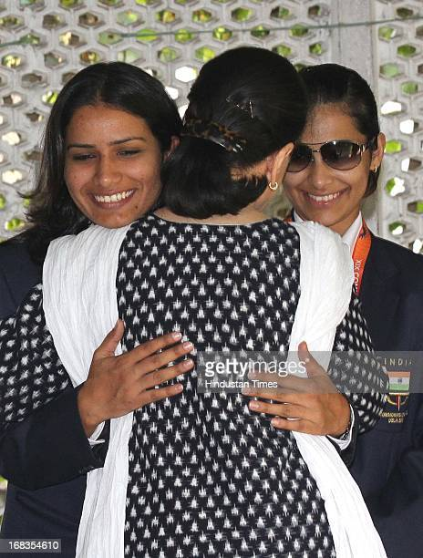 Congress President Sonia Gandhi hugs shooter Anu Raj Singh as another shooter Heena Sidhu looks on during a meeting with the Indian sportspersons who...