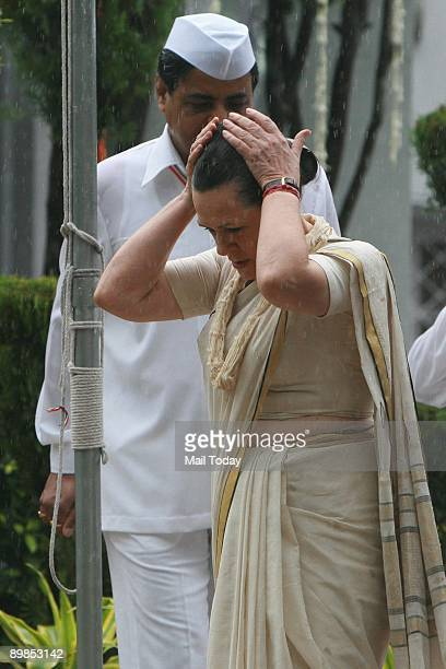Congress President Sonia Gandhi protects herself from the rain as she arrives to hoist the flag at the AICC headquarters on the 62nd Independence Day...