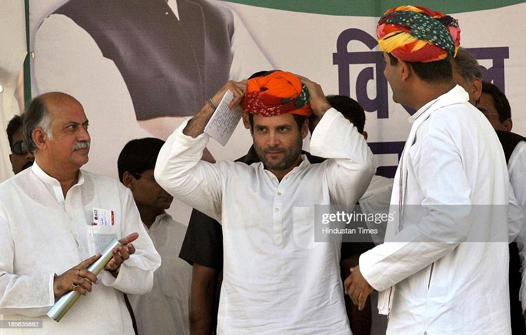 Congress Vice President Rahul Gandhi adjusts a turban gifted to him by Minister of State for Defence Jitendra Singh during his rally at Kherli on October 23, 2013 in Alwar, India. Addressing a rally in the poll-bound Rajasthan, Congress Vice President said the party's election manifesto will not be prepared in closed rooms this time around as people's suggestions will be included. On the occasion a website is launched by a 13 year old girl that will be used to collect feedback and suggestions from people for preparing the party's poll manifesto.