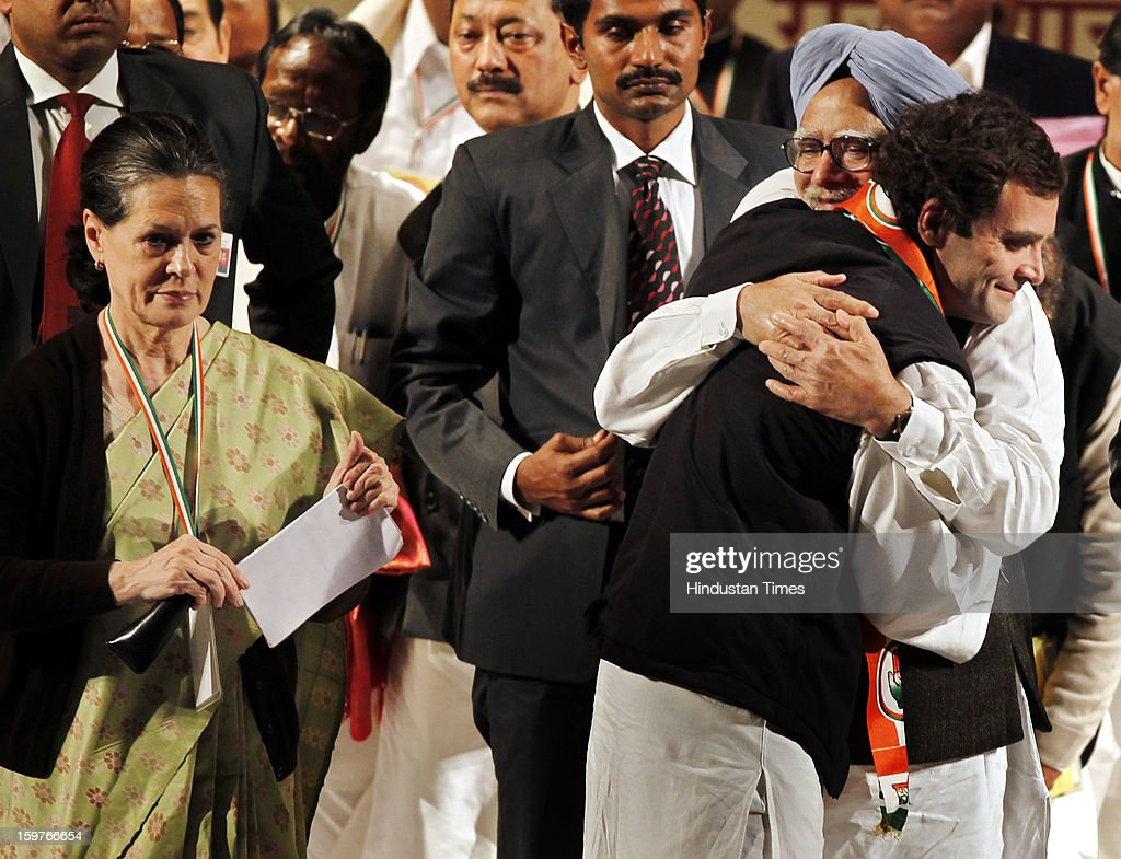 Congress Vice President Rahul Gandhi hugs Prime Minister Manmohan Singh while Congress President Sonia Gandhi looks on during the AICC meeting after the two days 'Chintan Shivir' at Birla Auditorium, Jaipur on January 20, 2013 in Rajasthan, India.