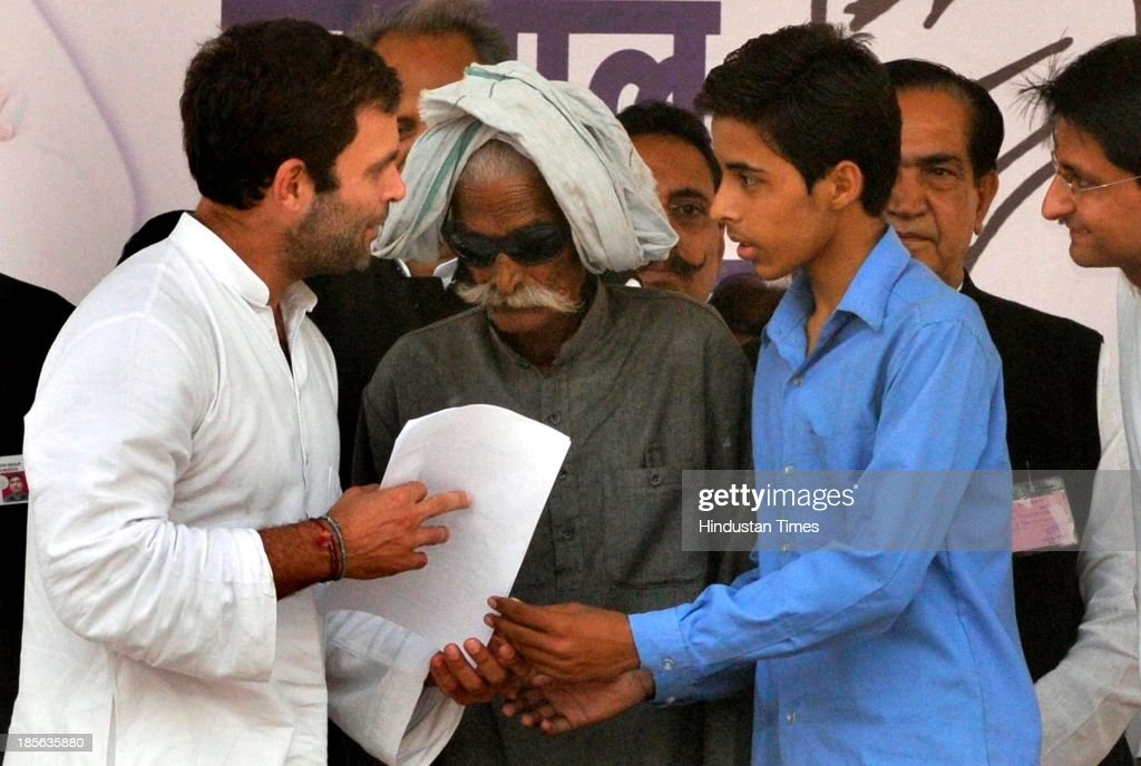 Congress Vice President Rahul Gandhi takes suggestion for party manifesto from a young boy and his grandfather during his rally at Kherli on October 23, 2013 in Alwar, India. Addressing a rally in the poll-bound Rajasthan, Congress Vice President said the party's election manifesto will not be prepared in closed rooms this time around as people's suggestions will be included. On the occasion a website is launched by a 13 year old girl that will be used to collect feedback and suggestions from people for preparing the party's poll manifesto.
