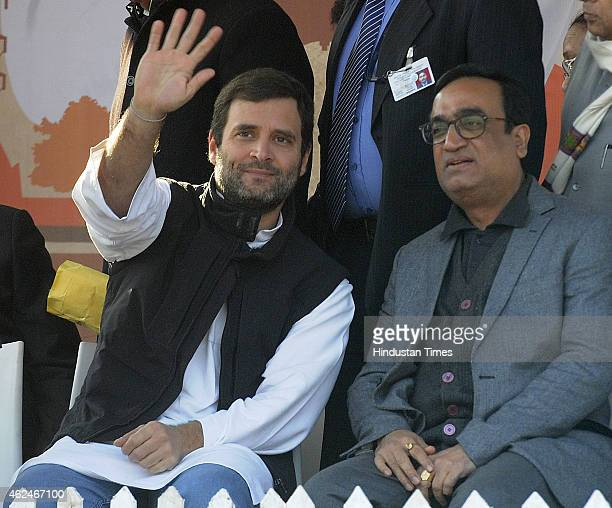 Congress VicePresident Rahul Gandhi waves at the supporters as Congress leader Ajay Maken looks on during an election rally for upcoming Delhi...