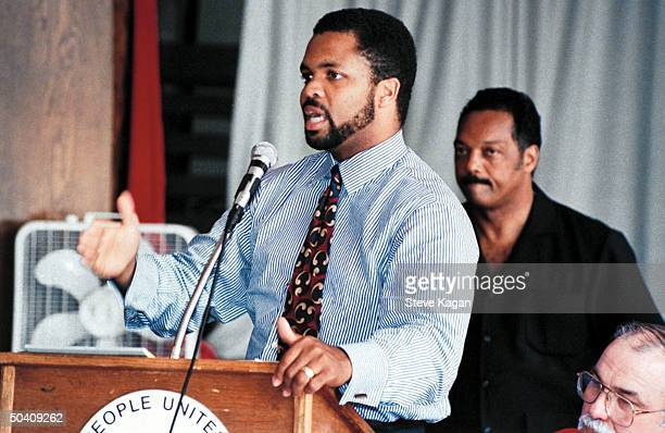 Congressional candidate Jesse Jackson Jr speaking at podium while his civil rights activist father Rev Jesse Jackson stands behind him