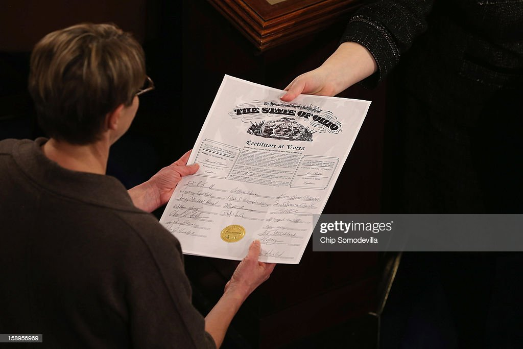 Congressional clerks pass the Electoral College certificate from the state of Ohio while unsealing and organizing all the votes from the 50 states in the House of Representatives chamber at the U.S. Capitol January 4, 2013 in Washington, DC. The votes were tallied during a joint session of the 113th Congress. President Barack Obama and Biden received 332 votes to be reelected.