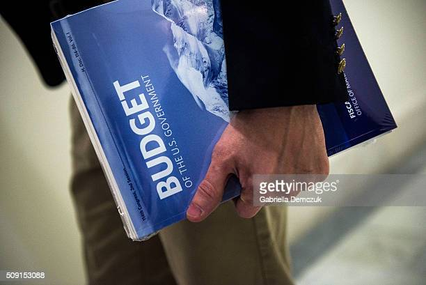 A congressional House staffer holds the President's Fiscal Year 2017 Budget in the House Budget Committee Room in the Cannon House Office Building on...