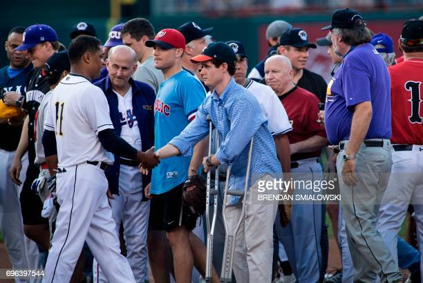 Congressional staff member Zack Barth who was wounded in yesterday's shooting is greeted by the Democrat's pitcher Rep Cedric Richmond DLA before the...