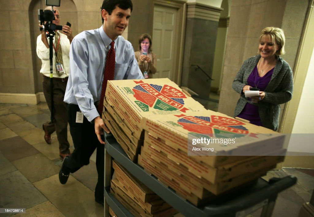 A Congressional staffer brings in a cart full of pizzas at the U.S. Capitol as both the Senate and House work on a deal to stop the government shutdown and avoid the country from defaulting October 15, 2013 on Capitol Hill in Washington, DC. The U.S. Government is on its 15th day of a shutdown.