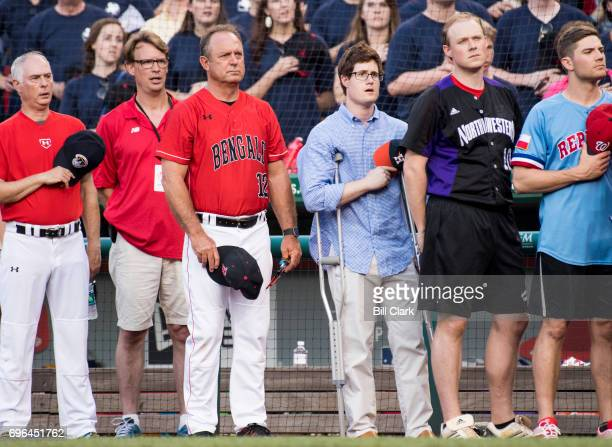 Congressional staffer Zach Barth center injured at the baseball practice shooting the day before stands during the annual Congressional Baseball Game...
