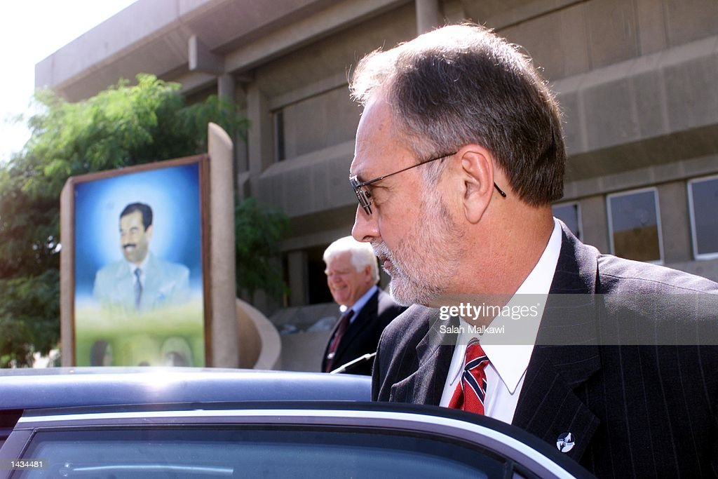 U.S. Congressman David E. Bonior (D-Mi) gets into a car with a poster of Saddam Hussein behind him September 27, 2002 in Baghdad, Iraq. Bonior and two other congressmen are in Iraq on a five-day visit to assess the humanitarian situation and to press for Baghdad to allow complete access to UN weapons inspectors to stave off a U.S. military intervention.