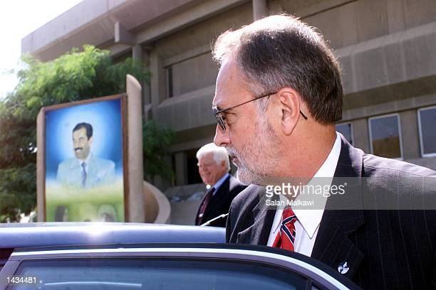 S Congressman David E Bonior gets into a car with a poster of Saddam Hussein behind him September 27 2002 in Baghdad Iraq Bonior and two other...