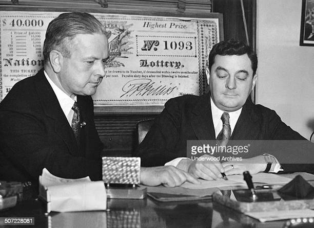 Congressman Edward Kenney of New Jersey watches Rep Joseph Gavagan of New York sign his petition calling for a vote on a national lottery to fund the...