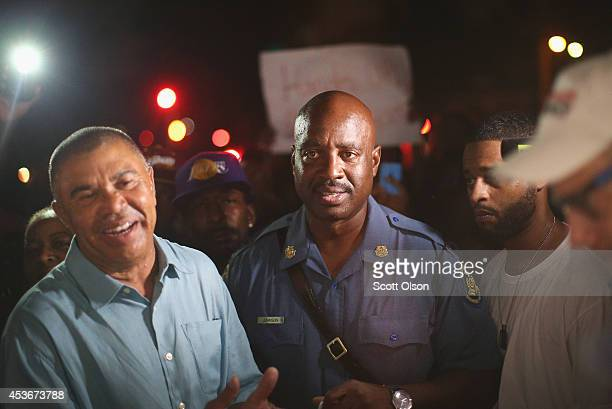 Congressman Lacy Clay and Capt Ronald Johnson of the Missouri State Highway Patrol speak to demonstrators gathered along West Florissant Avenue to...