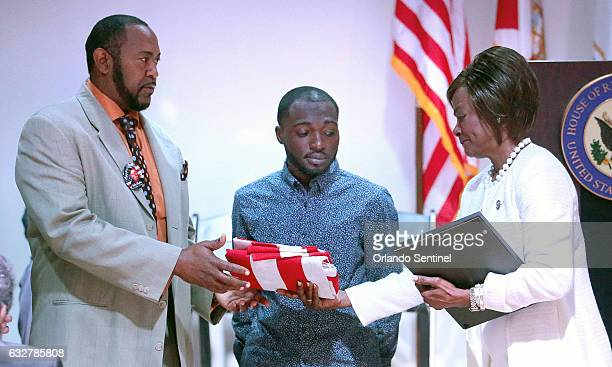 Congresswoman Val Demings right presents an official US Congressional American flag to the husband Seth Clayton and son Johnny Clayton of slain...