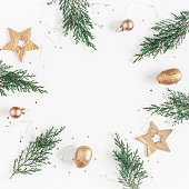 Christmas composition. Christmas frame made of conifer branches, balls, golden decorations on white background. Flat lay, top view, copy space, square