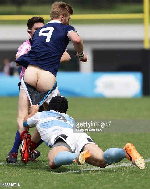 Conil Ignacio of Argentina pulls down Faraj Fartass of France during the Rugby Sevens Final on day four of the Nanjing 2014 Summer Youth Olympic...