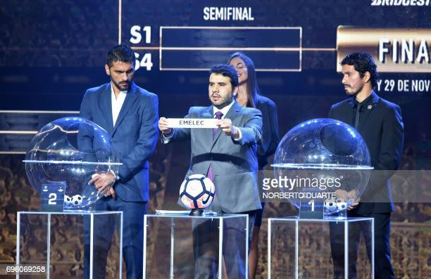 Conmebol Competitions' director Hugo Figueredo shows the name of Ecuadorean Emelec during the Libertadores Cup round of 16 draw in Luque Paraguay on...