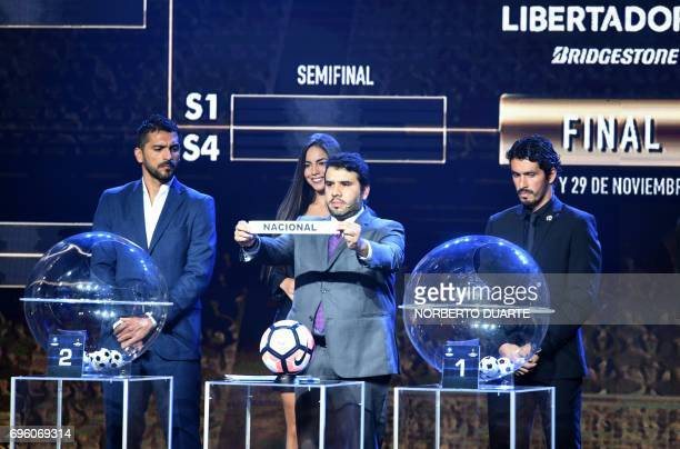 Conmebol Competitions' director Hugo Figueredo shows the name of Uruguayan Nacional during the Libertadores Cup round of 16 draw in Luque Paraguay on...