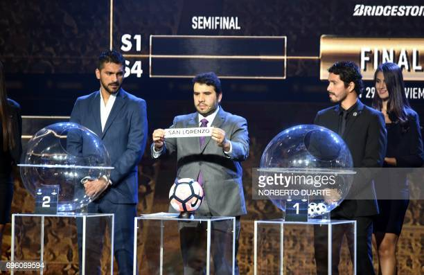 Conmebol Competitions' director Hugo Figueredo shows the name of Argentinian San Lorenzo during the Libertadores Cup round of 16 draw in Luque...
