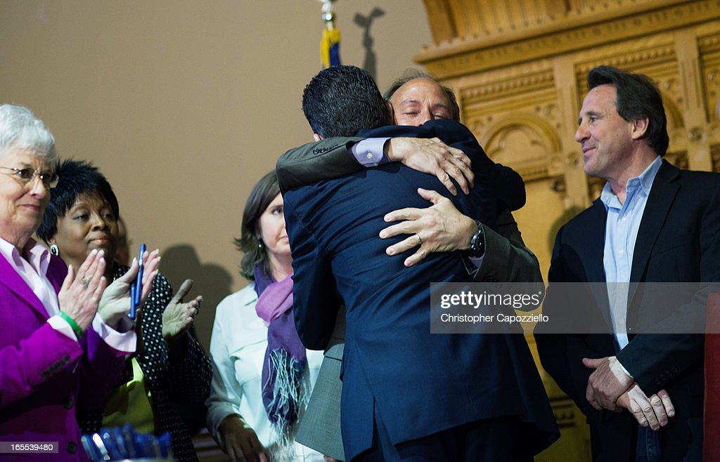 Connecticut Gov. Dannel Malloy (4th L) hugs Mark Barden (2nd R), the parent of a Sandy Hook shooting victim. after teh signing of a gun control law event at the Connecticut Capitol pril 4, 2013 in Hartford, Connecticut, After more than 13 hours of debate, the Connecticut General Assembly approved the gun-control bill early April 4, that proponents see as the toughest-in-the-nation response to the Demember 14, 2012 Newtown school shootings.