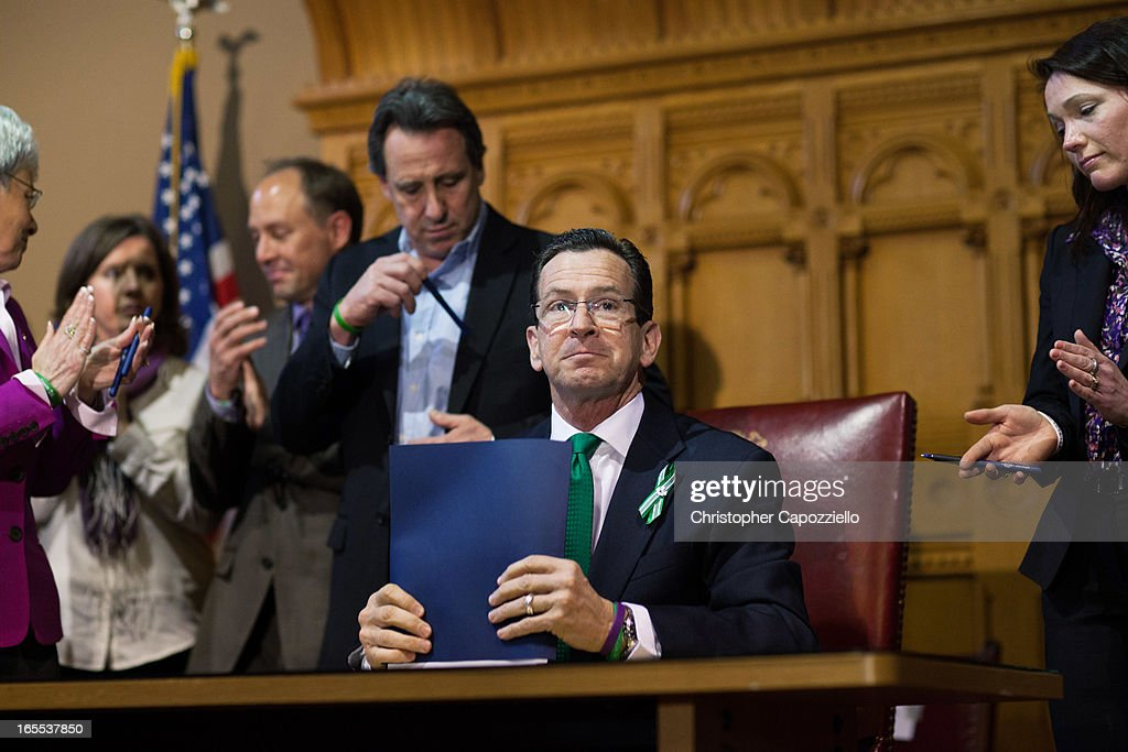 Connecticut Gov. Dannel Malloy (R) looks up after signing a gun-control bill April 4, 2013 in Hartford, Connecticut, After more than 13 hours of debate, the Connecticut General Assembly approved the gun-control bill early April 4, that proponents see as the toughest-in-the-nation response to the Demember 14, 2012 Newtown school shootings.