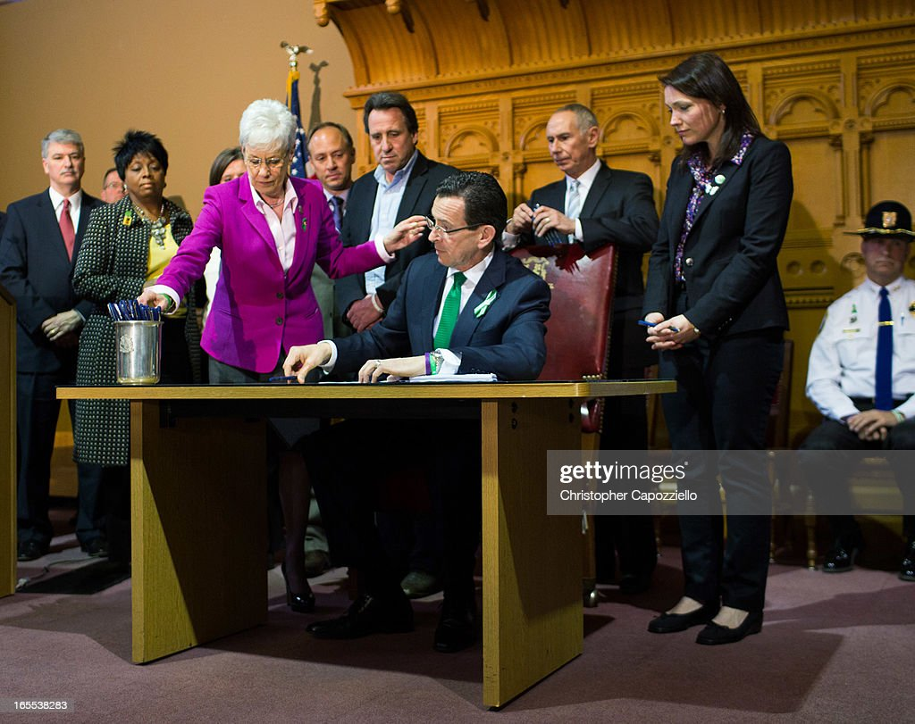 Connecticut Gov. Dannel Malloy (4th R) signs a gun-control bill as Connecticut Lieutenant Gov. Nancy Wyman (3rd L), Mark Barden (4th L), Neil Heslin (5th R), Nicole Hockley (2nd R) looks on April 4, 2013 at the Connecticut Capitol in Hartford, Connecticut. After more than 13 hours of debate, the Connecticut General Assembly approved the gun-control bill early April 4, that proponents see as the toughest-in-the-nation response to the Demember 14, 2012 Newtown school shootings.