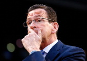 Connecticut governor Dannel Malloy talks with members of the national champion Connecticut Huskies men's basketball tem prior to the game between the...
