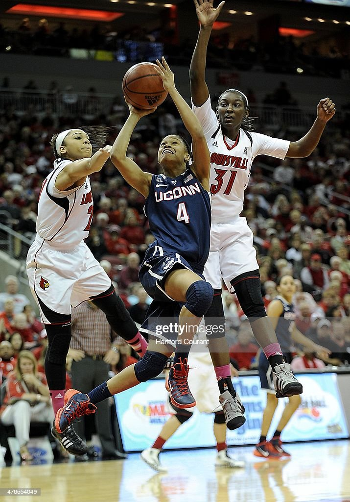 Connecticut Huskies guard Moriah Jefferson (4) finds a seam between Louisville Cardinals guard Bria Smith (21) and Louisville Cardinals forward Asia Taylor (31) during the first half at the KFC Yum Center in Louisville, Ky., on Monday, March 3, 2014.