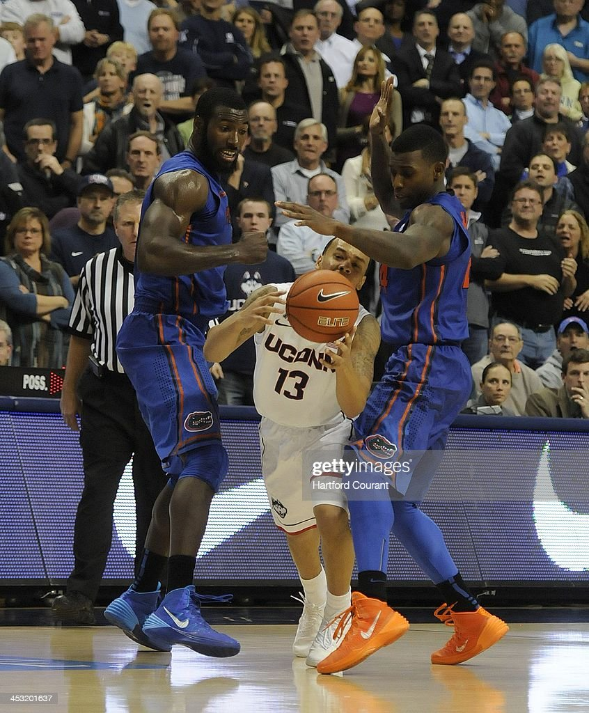 Connecticut Huskies' Shabazz Napier breaks out of a trap of Florida Gators players Patric Young, left, and Casey Prather in the closing seconds of the game at Gampel Pavillion in Storrs, Conn., on Monday, Dec. 2, 2013. UConn won, 65-64.