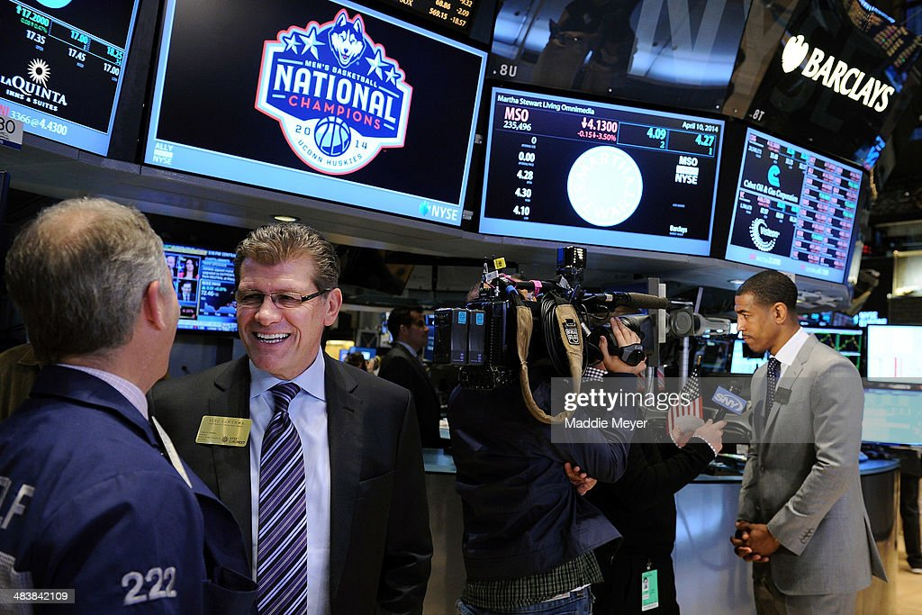 Connecticut Huskies Women's basketball Coach Geno Auriemma talks with a Wall Street trader while Connecticut Huskies Men's basketball Coach Kevin Ollie (R) is interviewed at New York Stock Exchange on April 10, 2014 in New York City.