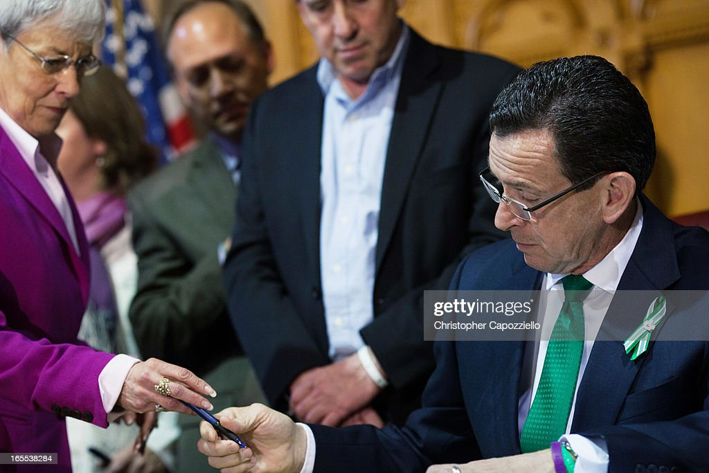Connecticut, Lieutenant Gov. Nancy Wyman (L) takes a pen from Connecticut Gov. Dannel Malloy (R) as he signs a gun-control bill at the Connecticut Capitol April 4, 2013 in Hartford, Connecticut. After more than 13 hours of debate, the Connecticut General Assembly approved the gun-control bill early April 4, that proponents see as the toughest-in-the-nation response to the Demember 14, 2012 Newtown school shootings.