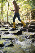 USA, Connecticut, Newtown, Woman walking on rocks in stream