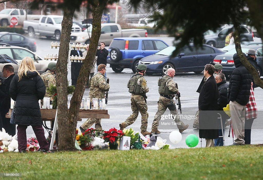 Connecticut State Police officers walk past a makeshift memorial to shooting victims while searching outside St. Rose of Lima Roman Catholic Church after a threat to the church was received during the first day of Sunday services following the mass shooting at Sandy Hook Elementary School on December 16, 2012 in Newtown, Connecticut. The church was evacuated during noon mass due to the unspecified threat and will remain closed the rest of the day. Adam Lanza and eight of the shooting victms attended the church. Police have reportedly now given the 'all clear' for the area.