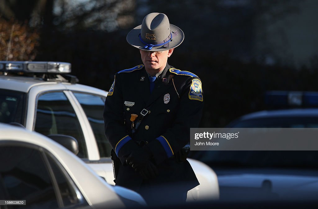 A Connecticut state policeman pays his respects outside a wake for Jesse Lewis, 6, on December 20, 2012 in Newtown, Connecticut. Jesse was killed when 20 children and six adults were massacred at Sandy Hook Elementary School last Friday. Firemen, police and and counselors from around state and the country have come to assist Newtown authorities with the aftermath of the tradegy.