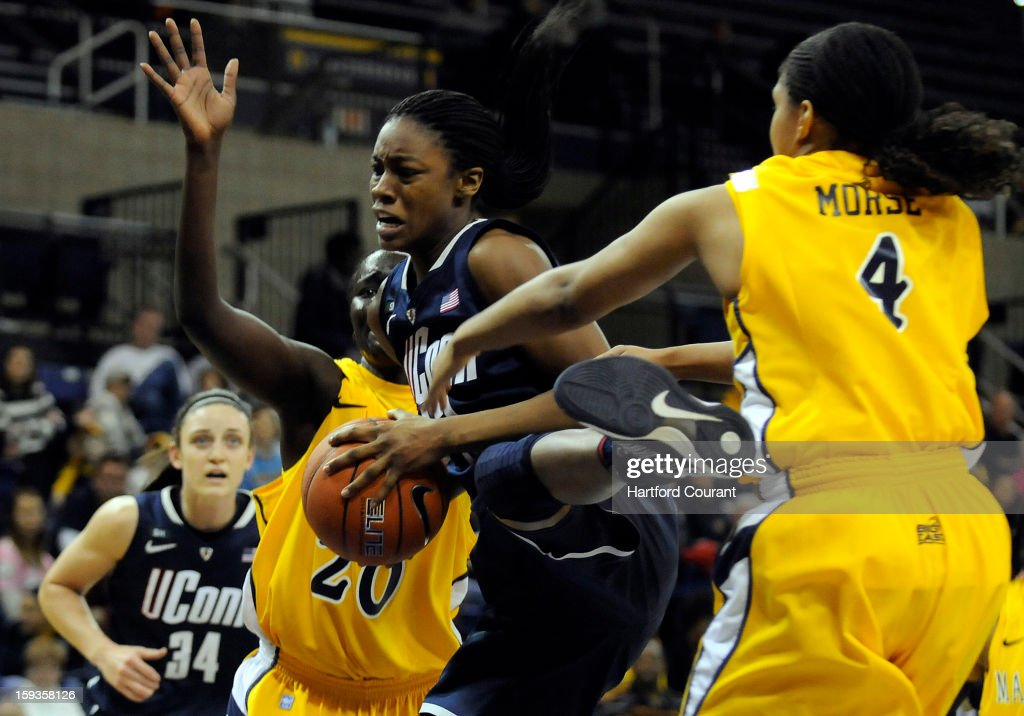 Connecticut's Brianna Banks grabs an offensive rebound in between Marquette's Apiew Ojulu (20) and Arlesia Morse (4) during the first half at the Al McGuire Center in Milwaukee, Wisconsin, on Saturday, January 12, 2013.