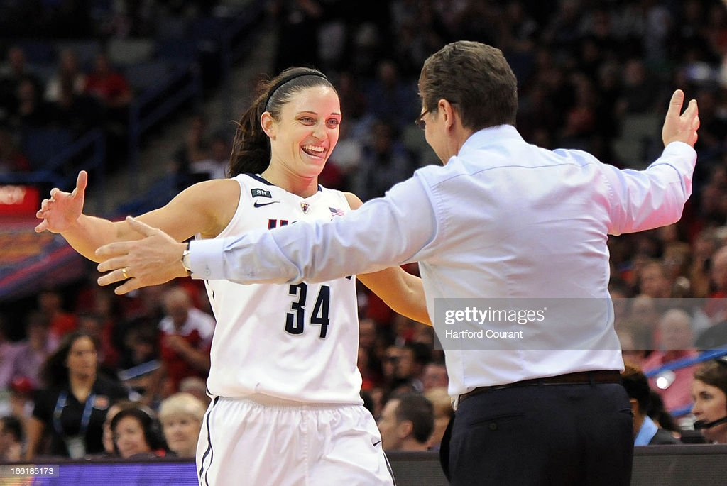 Connecticut's Kelly Faris (34) is congratulated by head coach Geno Auriemma as she leaves the game late in a 93-60 win against Louisville in the women's NCAA Tournament finals at New Orleans Arena in New Orleans, Louisiana, Tuesday, April 9, 2013.