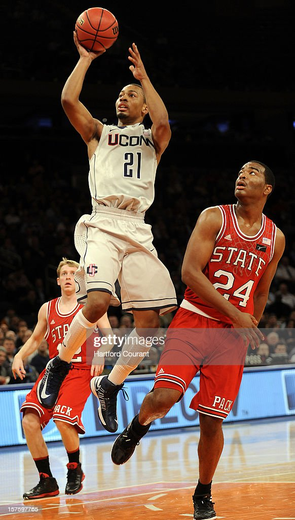 Connecticut's Omar Calhoun (21) drives to the basket and is fouled by North Carolina State's T.J. Warren (24) during the first half of the Jimmy V Classic on Tuesday, December 4, 2012, at Madison Square Garden in New York.