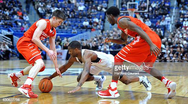Connecticut's Rodney Pervis battles for a loose ball against Houston's Wes Vanbeck left and Damyean Dotson in the first halfat XL Center in Hartford...