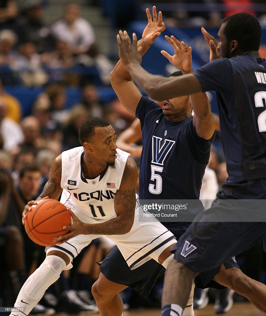 Connecticut's Ryan Boatright looks for help while beging double teamed by Villanova guard Tony Chennault and forward Daniel Ochefu in the first half at the XL Center in Hartford, Connecticut, Saturday, February 16, 2013. Villanova defeated UConn, 70-61.