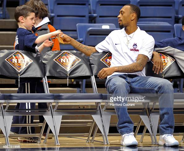 Connecticut's Ryan Boatright signs an autograph for a young fan before a firstround NIT Tournament game against Arizona State at Gampel Pavilion in...