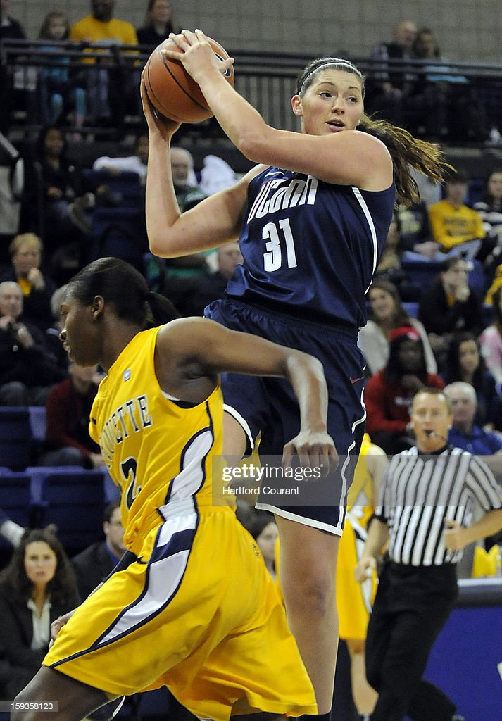 Connecticut's Stefanie Dolson (31) dishes off as Marquette's Sarina Simmons (42) defends during the first half at the Al McGuire Center in Milwaukee, Wisconsin, on Saturday, January 12, 2013.
