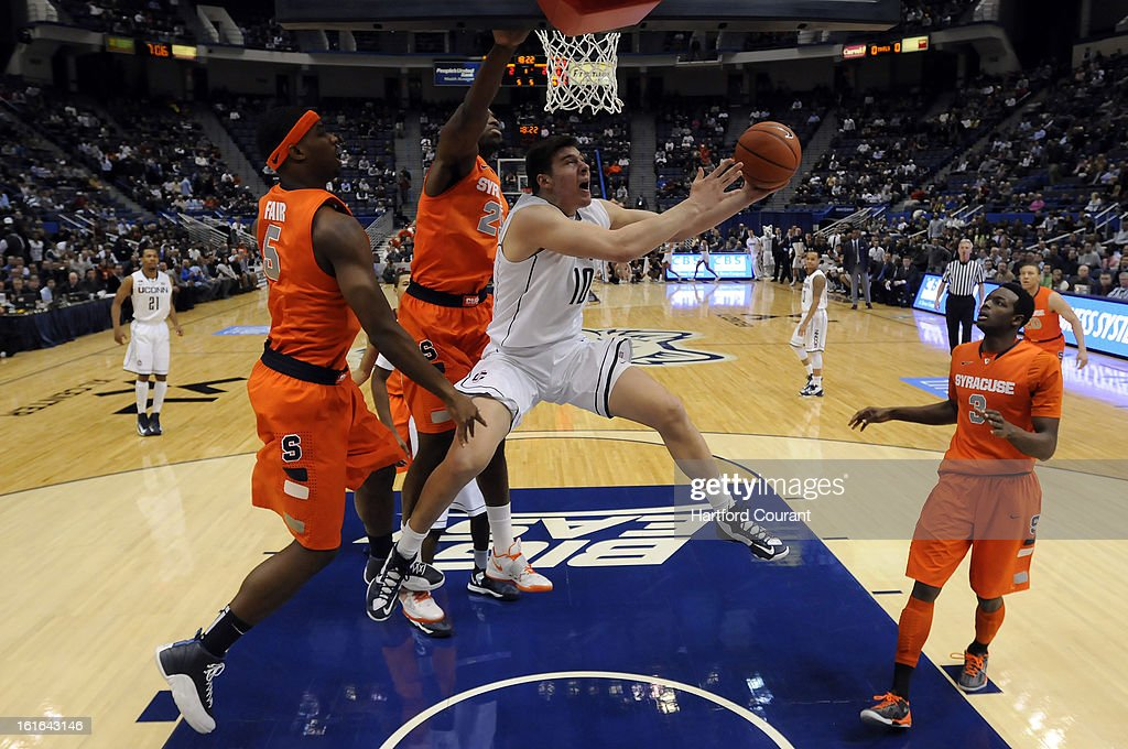 Connecticut's Tyler Olander (10) slides past Syracuse's C.J. Fair (5) and Rakeem Christmas (25) during the first half on Wednesday, February 13, 2013, at the XL Center in Hartford, Connecticut. UConn defeated Syracuse, 66-58.