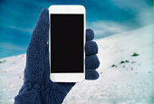 hand with fleece glove holding the smartphone with snow mountain in background. Skier on the mountain connecting with your phone
