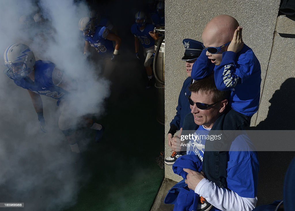 Conner Arnold, 5, covers his ears while on his dad's shoulders, Air Force Major, Eric Arnold, while Conner's brother, Air Force cadet. Christian Arnold, watches his team, the Air Force Falcons, take the field to play Notre Dame at Falcon Stadium Saturday afternoon, October 26, 2013. Conner is battling Ewings Sarcoma cancer an had a chance to get a first-hand look at his favorite team Saturday afternoon.